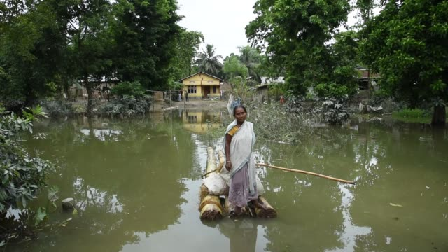 july 2020. a woman crossing a flooded area by banana raft, due to monsoon rains, in a flood affected village morigaon district of assam, india, 20... - 重い点の映像素材/bロール