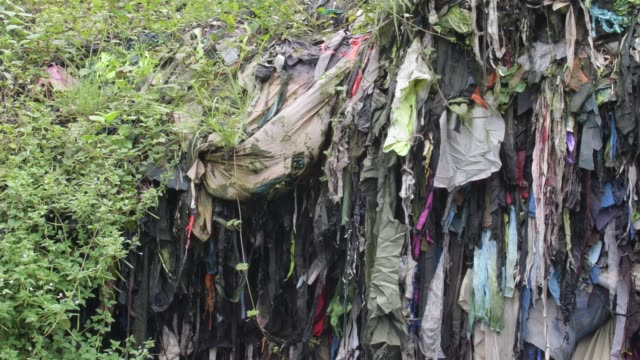 july 2020: garment factory waste at a dumping site in dhaka. - textilindustrie stock-videos und b-roll-filmmaterial