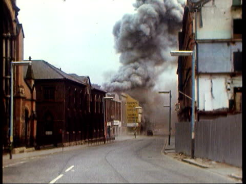 vidéos et rushes de july 23, 1972 city street as ira bomb goes off on bloody friday/ people walking through debris-strewn street/ man running across street/ soldiers... - bombardement