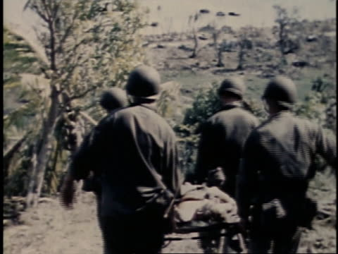 july 24 1944 montage four soldiers carrying a stretcher and large group of soldiers walking around relaxed / guam - campo militare video stock e b–roll