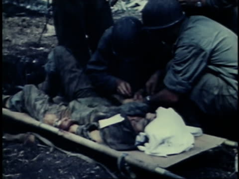 vídeos y material grabado en eventos de stock de july 24, 1944 montage military men evaluating and working on an injured man on a stretcher / guam - brazo humano