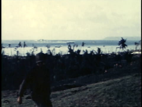 july 24 1944 pan view of field with military walking around during nightfall with a view of he ocean behind / guam - guam stock videos & royalty-free footage