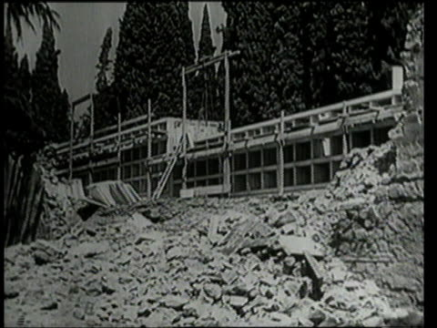 stockvideo's en b-roll-footage met july 25 1943 montage people gathering at a new construction site next to a huge bomb crater filled with rubble / rome italy - 1943
