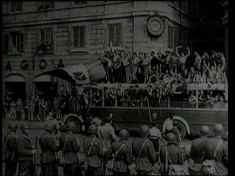 july 25, 1943 montage vehicles filled flag-waving, cheering people driving up street / rome, italy - anno 1943 video stock e b–roll