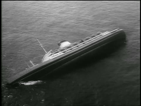 vidéos et rushes de b/w july 26 1956 aerial over ship andrea doria on its side in ocean after crash / newsreel - 1956