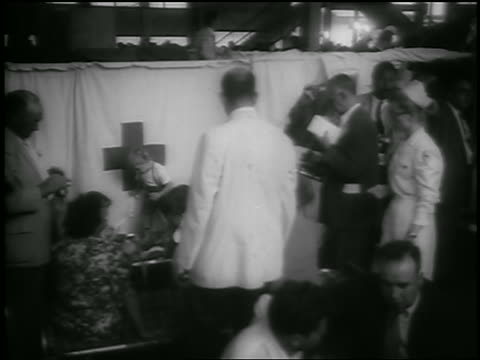 vídeos de stock e filmes b-roll de july 26, 1956 doctor + others in makeshift clinic in pier waiting room after andrea doria crash - 1956