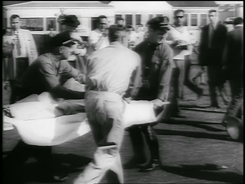 b/w july 26 1956 pan men carry injured person on stretcher outdoors after andrea doria crash - 1956 stock videos and b-roll footage