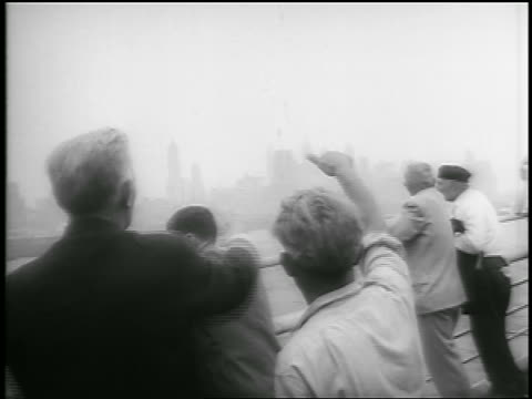 vídeos y material grabado en eventos de stock de july 26, 1956 rear view 2 men on ship deck wave + blow kiss at nyc / survivors of andrea doria - only mature men