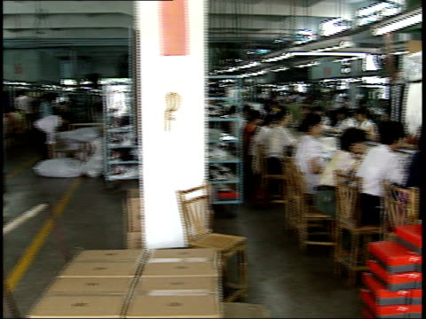 july 26, 1993 packaging warehouse, workers sitting at work stations in assembly line, worker bringing boxes to the line while another worker passes... - warehouse点の映像素材/bロール