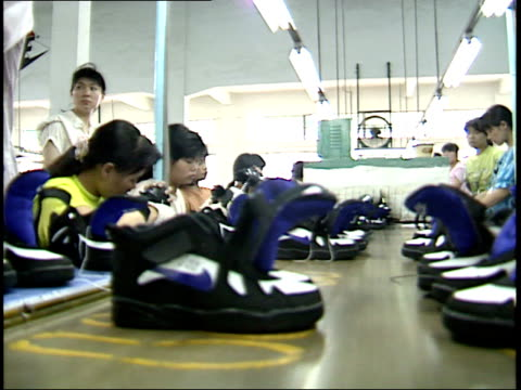 vídeos de stock, filmes e b-roll de july 26 1993 la workers producing and checking the quality of training shoes in a nike factory / china - enfoque de objeto sobre a mesa