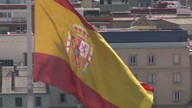 July 3 2010 HA Spanish flag waving in the wind above city buildings / Madrid Spain