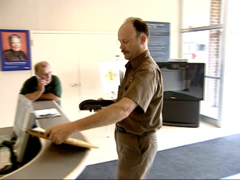 stockvideo's en b-roll-footage met july 31, 2006 ups delivery man delivering a package to an office and having the receptionist sign for it / united states - e mail
