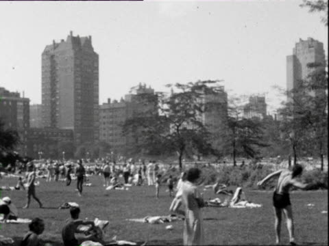 july 4, 1938 b/w ws pan people relaxing on grass by water / chicago, illinois, usa - 1938 stock videos & royalty-free footage