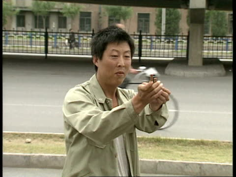 july 6 1989 film montage ms zi man holding bullets up to camera/ ws zi broken windows following tiananmen square protests/ zo windows/ beijing china/... - anno 1989 video stock e b–roll