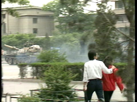 vídeos de stock, filmes e b-roll de july 6, 1989 film montage tanks passing on road in response to tiananmen square protestors as pedestrians watch from sidewalk/ civilians marching on... - 1980 1989