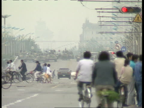 vídeos de stock, filmes e b-roll de july 6, 1989 film montage traffic and pedestrians on street with line of tanks in background as a military response to tiananmen square protests/... - 1980 1989