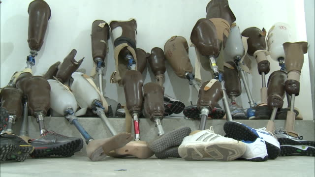 july 7 2010 ws group of prosthetic legs some with shoes and some without leaning against wall / haiti - haiti stock videos & royalty-free footage