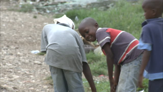 july 7 2010 ts local children carrying heavy water jug along a gravel path towards a tent camp / haiti - haiti stock-videos und b-roll-filmmaterial