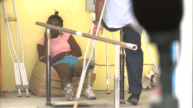 vídeos y material grabado en eventos de stock de july 7, 2010 local with prosthetic leg sitting against the wall and another on crutches standing / haiti - formato buzón