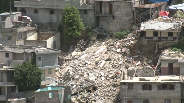 july 7, 2010 montage damaged rooftops and a large pile of rubble among collapsed homes on hillside / haiti - 2010 個影片檔及 b 捲影像