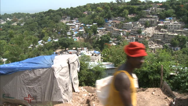 vídeos de stock, filmes e b-roll de july 7 2010 montage villagers walking along a steep path near makeshift shelters a red cross aid tent and a worker scooping rubble into a sack / haiti - 2010