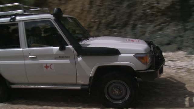 july 7 2010 ts red cross jeep driving down a rocky dirt road next to embankment as villagers look on / haiti - 赤十字社点の映像素材/bロール