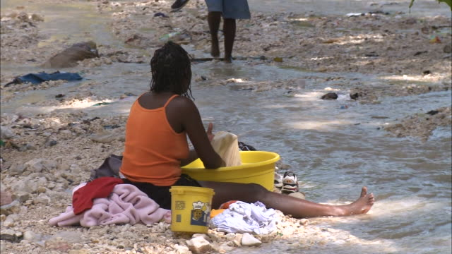 vídeos de stock, filmes e b-roll de july 7 2010 ws villager sitting in sand along puddles on a shore washing clothes in a tub / haiti - 2010