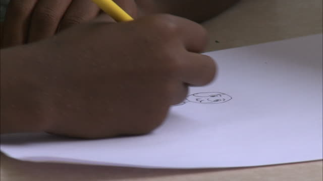 july 7 2010 cu young child drawing and coloring a picture of a man / portauprince haiti - ポルトープランス点の映像素材/bロール