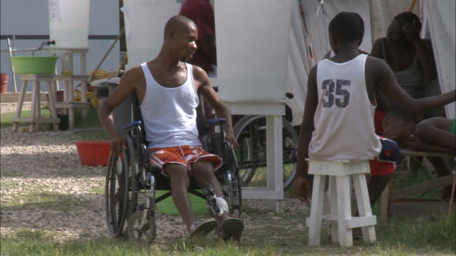 vídeos de stock, filmes e b-roll de july 8 2010 ts earthquake victim in wheelchair pushing himself through tent city / republic of haiti - 2010