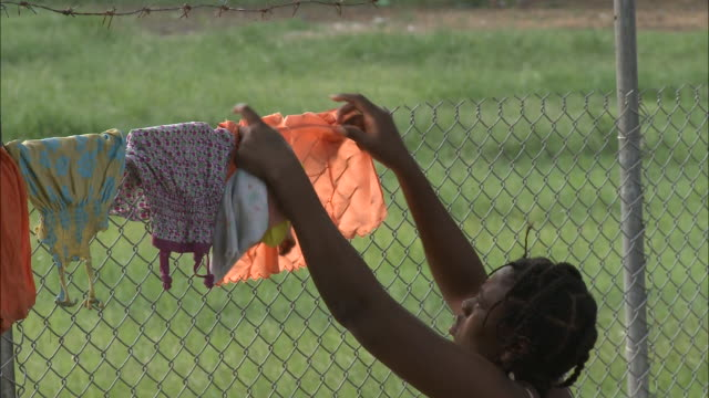 stockvideo's en b-roll-footage met july 8 2010 ms mother hanging laundry on the fence / portauprince haiti - hangen