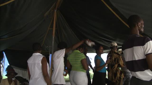 vídeos y material grabado en eventos de stock de july 9 2010 pov earthquake survivors waiting in lines for supplies draped across folding tables under a tent / haiti - 2010