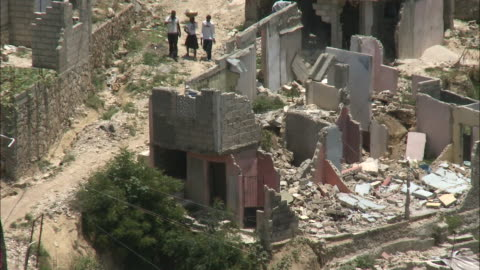 stockvideo's en b-roll-footage met july 9, 2010 montage locals walking on dirt roads past damaged, crumbled buildings sitting amongst rubble / haiti - 2010