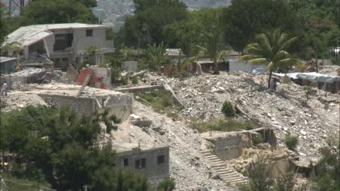 stockvideo's en b-roll-footage met july 9, 2010 montage locals walking through ruins of destroyed buildings / haiti - 2010