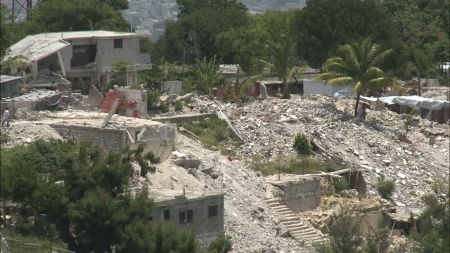 vídeos de stock, filmes e b-roll de july 9 2010 montage locals walking through ruins of destroyed buildings / haiti - 2010