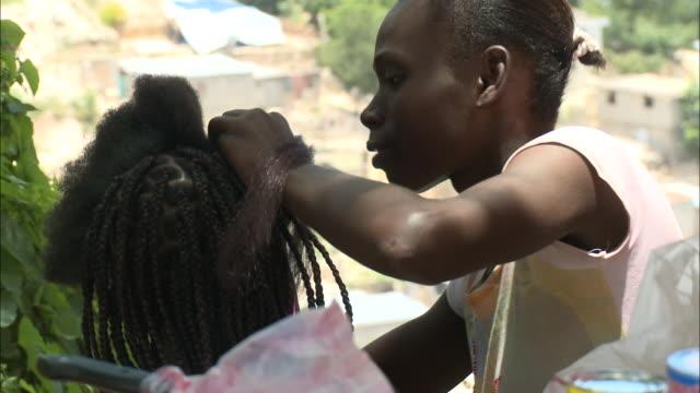 July 9 2010 MS Stylist braiding a local's hair / Haiti