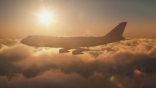 vídeos de stock e filmes b-roll de jumbo jet above the clouds with sun - avião comercial