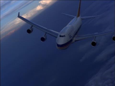 Jumbo jet banks over clouds