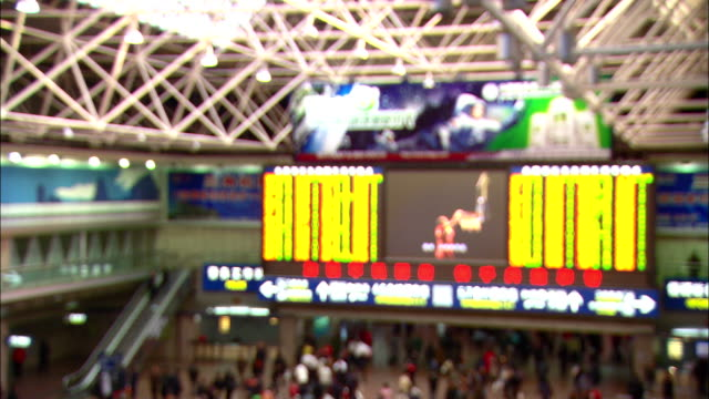 a jumbotron entertains commuters in a crowded subway station. - large scale screen stock videos & royalty-free footage