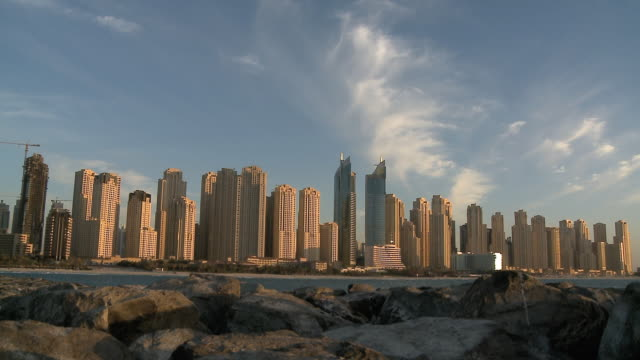 t/l ws jumeirah beach residences and al fattan towers seen across water, day to dusk / dubai, united arab emirates - zeitraffer tag bis dämmerung stock-videos und b-roll-filmmaterial