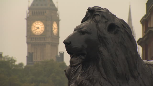 jump cut sequence showing bronze lions of trafalgar square set against 'big ben', westminster, london, uk. - british flag stock videos & royalty-free footage