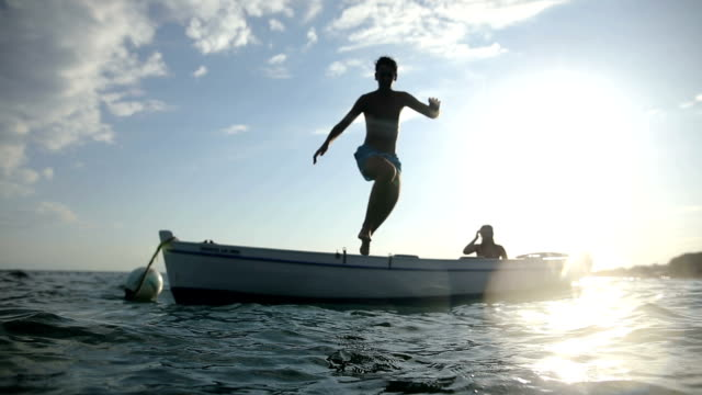 Jump from the boat at sunset