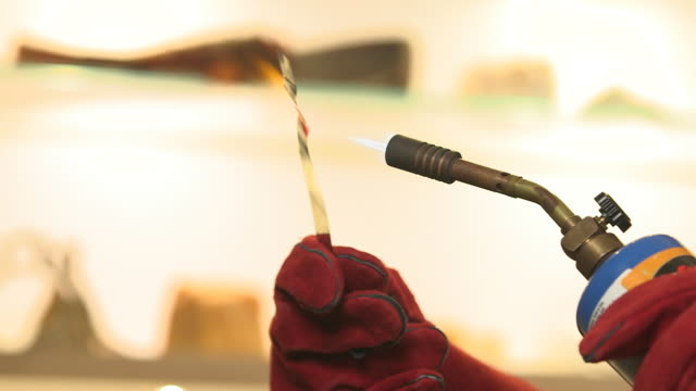 Jump-cut close-up sequence showing heat being applied to a thin strip of steel with a blowtorch, UK.