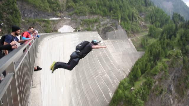 vidéos et rushes de base jumper descends from high concrete dam to valley below - exploit sportif