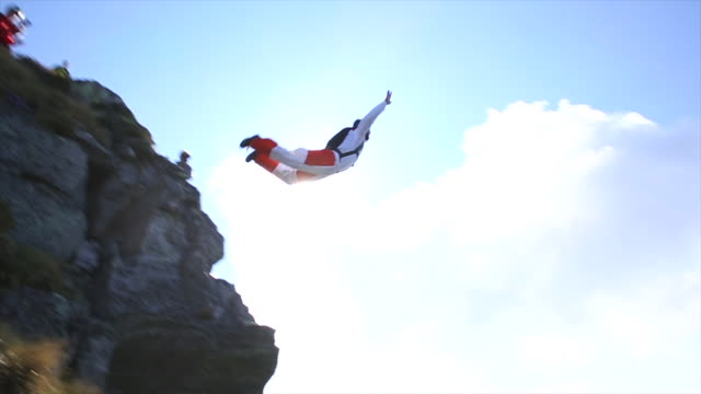 BASE jumper in mid air flight from mountain summit