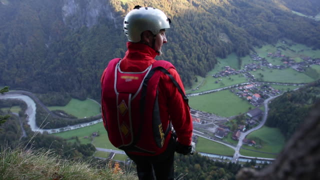 base jumper plunges from cliff edge, mountains - base jumper stock videos & royalty-free footage