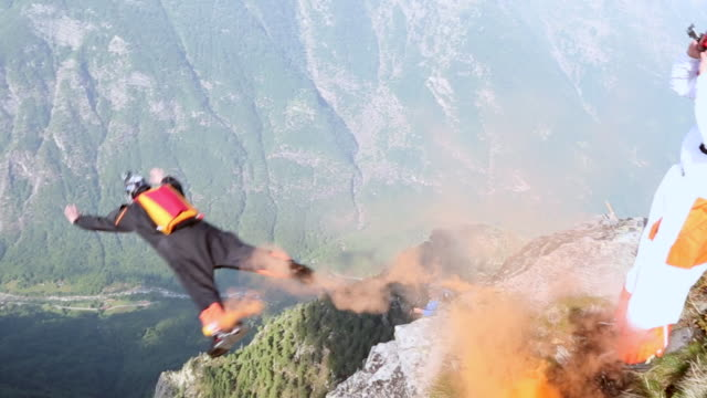 BASE jumper plunges from mountain summit, trailing smoke