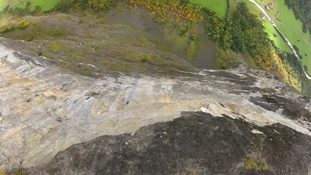 POV of BASE jumper plunging down vertical cliff