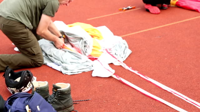 base jumper prepares parachute for jump, parking area - parachuting stock videos and b-roll footage