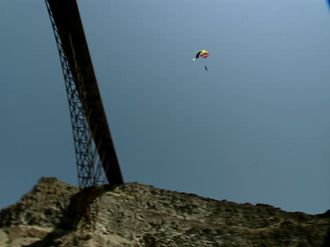 a base jumper sails off the perrine bridge and down into the grassy gorge below. - base jumper stock videos & royalty-free footage
