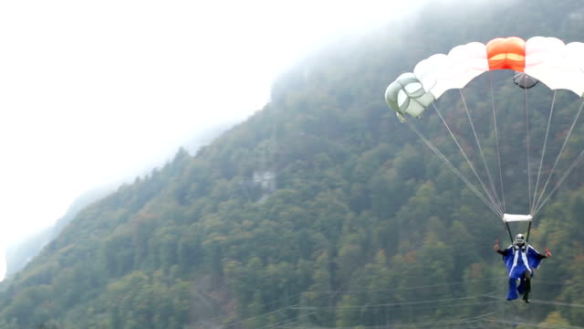 base jumper/wing suit flier descends from cliff - base jumper stock videos & royalty-free footage
